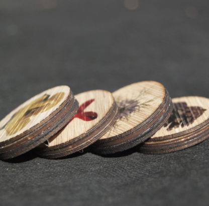 Image of four wooden pin badges in a row
