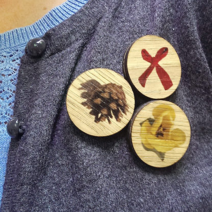 Image of three styles of wooden pin badges worn on a cardigan