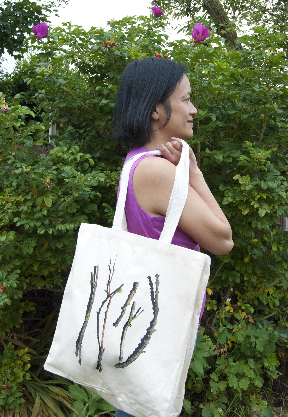 Image of woman holding a canvas bag featuring sticks and twigs design