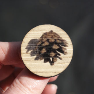Image of pin badge featuring pine cone photo design