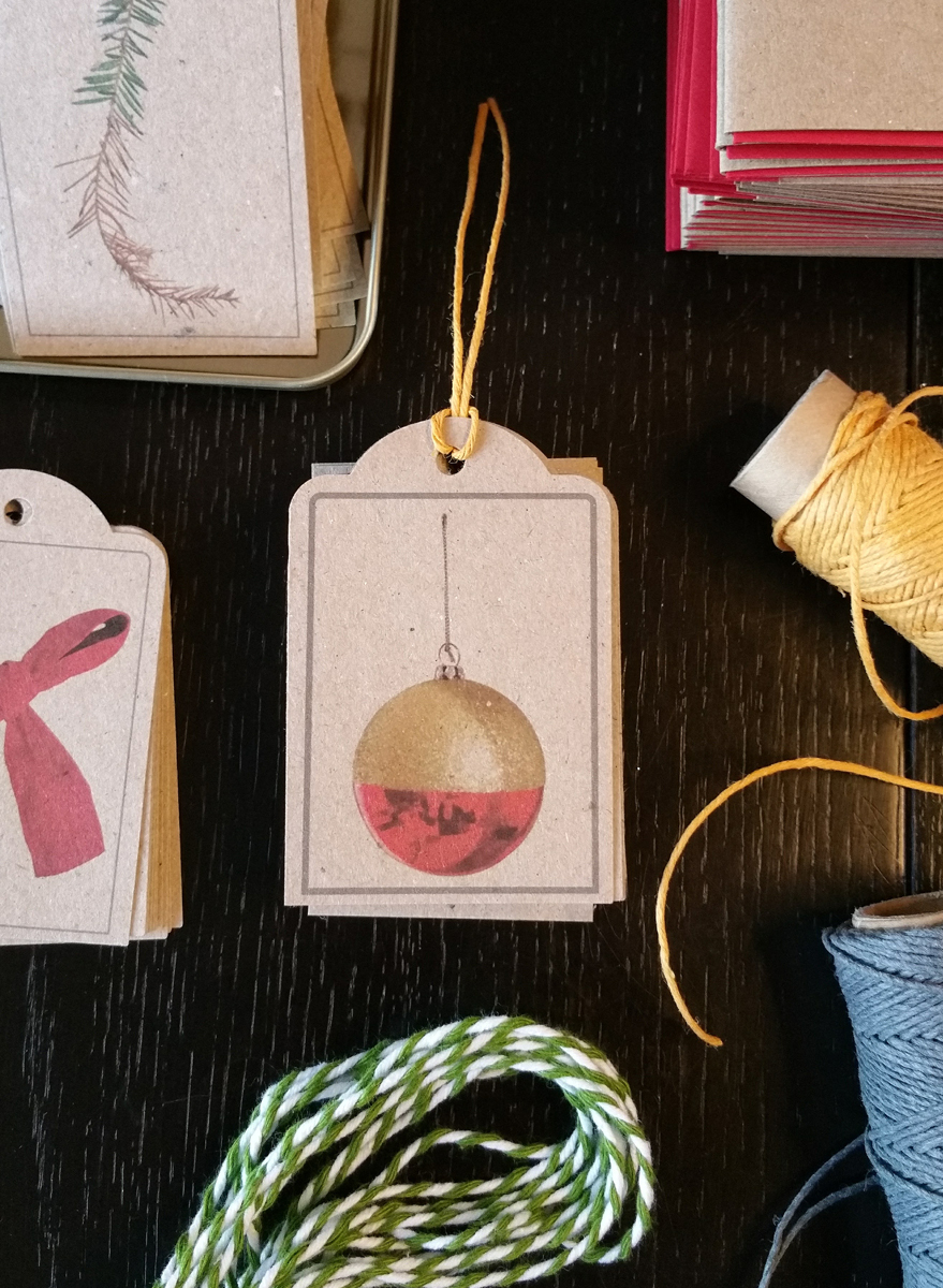 Photo of gift tags featuring a red and gold Christmas bauble