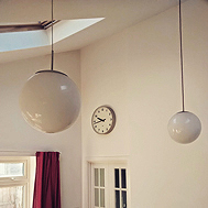 Photo of living room with two globe lights and an analogue round wall clock