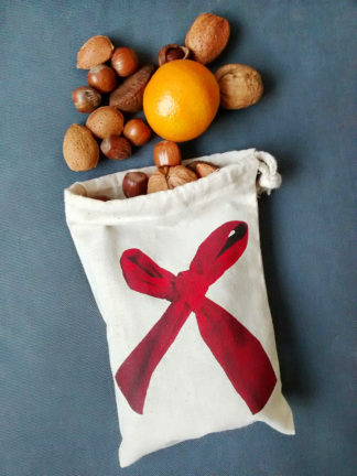 Drawstring bag with red ribbon bow design spilling nuts and fruit
